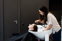 Cheveux de séchage de femme de jeune styliste féminin avec de l'eau dans le raseur-coiffeur de salon Photographie stock libre de droits