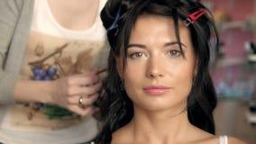 Cheveux de séchage de styliste d'un client féminin au salon de beauté Belle brune de mannequin Photographie stock