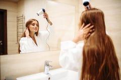 Cheveux de séchage de femme avec le dessiccateur dans la salle de bains photo libre de droits
