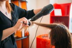 Cheveux de séchage de styliste avec un dessiccateur, coiffure image libre de droits
