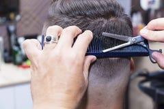 Cheveux du ` s d'hommes dénommant et se toilettant à l'aide des ciseaux machine et des tondeuses dans le salon de coiffure Images libres de droits