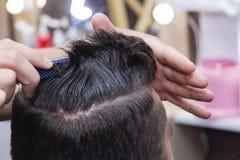 Cheveux du ` s d'hommes dénommant et se toilettant à l'aide des ciseaux machine et des tondeuses dans le salon de coiffure Photos stock
