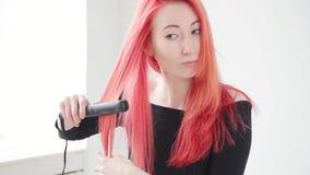 Cheveux et concept de coiffure La jeune femme avec les cheveux rouges cr?e une coiffure avec du fer ou des pinces banque de vidéos