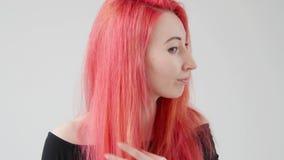 Cheveux et concept de coiffure La jeune femme avec les cheveux rouges cr?e une coiffure avec du fer ou des pinces clips vidéos