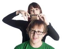 Cheveux femelles de coupe de coiffeur d'un homme inquiété photo stock