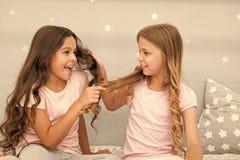 Cheveux forts Jeu gai d'enfants avec des cheveux dans la chambre ? coucher Moments heureux d'enfance Badine des meilleurs amis de photos stock