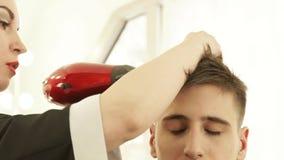 Cheveux masculins de séchage de styliste en coiffure après coiffure dans le salon de coiffure Fermez-vous vers le haut du coiffeu banque de vidéos