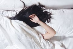 Cheveux noirs de femme dormant sur l'oreiller blanc de couleur et le lit Image libre de droits