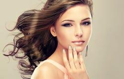 Cheveux onduleux et denses et manucure de style français Photographie stock