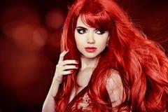 Cheveux rouges de coloration. Façonnez le portrait de fille avec les longs cheveux bouclés OV Photographie stock