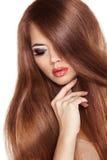 Cheveux rouges. Femme de beauté avec B lisse sain et brillant très long Image stock