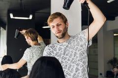 Cheveux séchants de sourire professionnels du ` s de femme de styliste masculin avec un dessiccateur dans le salon images stock