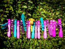 Chevilles en plastique de caractère coloré sur une ligne Photos stock