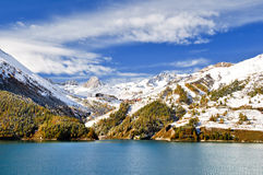 Chevril lake and Tignes. Behind between snow and orange larch Stock Photo