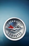 Chevrolet Corvette brand. Old Chevrolet Corvette round hood logo with racing flags. Blue copyspace over the brand Royalty Free Stock Photos