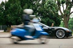 Chevrolet Corvette ZR1 que está sendo admirado pelo homem no 'trotinette' no movimento Imagens de Stock Royalty Free