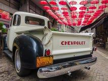 Chevrolet e umbrelas vermelhos Fotografia de Stock Royalty Free