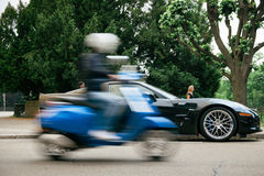 Chevrolet korweta ZR1 podziwia mężczyzna na hulajnoga w ruchu Obrazy Royalty Free