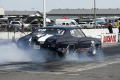 Chevrolet malibu burnout. Rear side view of black chevrolet malibu making a smoke show on the track during the festidrag event at napierville dragway Royalty Free Stock Images