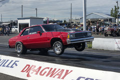 Drag racing. Side view of red chevrolet malibu making a wheelie on the track Stock Photography