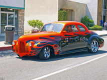 1945 Chevrolet. This is a nicely customized red and black 1945 Chevrolet two door sedan with a spectacular paint job and cool after market wheels Stock Photography