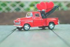 Chevrolet röd lastbilleksak som bär röd hjärta på trägolvet Royaltyfria Foton