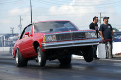 Drag racing. Napierville dragway august 23, 2014 picture of red chevrolet malibu making a wheelie at starting line during drag show at john scotti all out event Stock Photos