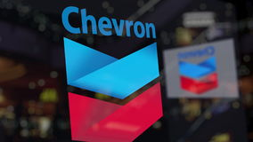 Chevron Corporation logo on the glass against blurred business center. Editorial 3D rendering Stock Images