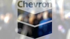 Chevron Corporation logo on a glass against blurred crowd on the steet. Editorial 3D rendering. Chevron Corporation logo on a glass against blurred crowd on the stock video