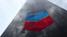 Chevron Corporation logo on a skyscraper facade reflecting clouds, time lapse. Editorial 3D rendering. Chevron Corporation logo on a skyscraper facade reflecting stock footage