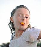 Chew and Show. Freckled girl with wet hair shows off orange wedge in her mouth Royalty Free Stock Photo