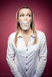 Chewing gum. Young woman making a chewing gum bubble and looking right Stock Photo