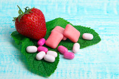 Chewing gum. And strawberry with mint and candy on wooden background stock photos