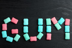 Chewing gum. Turquoise and red with blue gum in the form of cushions on black wooden background stock image