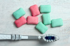 Chewing gum. Turquoise and red chewing gum on a white wooden background with a toothbrush stock images