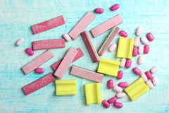 Chewing gum. Yellow and pink chewing gum with small candies on a blue wooden background stock photos