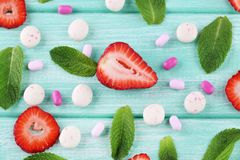 Chewing gums. With mint leafs and strawberries on wooden table stock photos