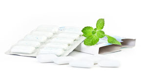 Chewing gym and  leaves of mint. Chewing gym and fresh leaves of mint on a white background Stock Images