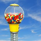 Chewinggumball machine. Gumball machine with colorful chewing gum balls on sqaure blue sky background Stock Photography