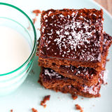 Chewy chocolate and coconut slice. And milk in glass, square image royalty free stock photography