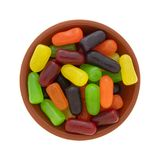 Chewy colorful candy in a bowl. Top view of a small bowl filled with chewy colorful sugar candy isolated on a white background royalty free stock photos
