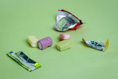 Chewy Fruity Candy. Strawberry, grape, banana and green apple chewy candies and their open wrappers on a green background royalty free stock photos