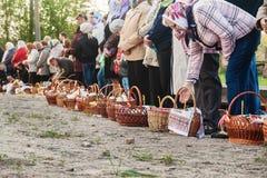 Chez Pâques beaucoup de personnes se tenant dans une rangée avec des paniers et des bougies, attendant le prêtre pour bénir L'Ukr Photographie stock libre de droits