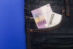 CHF and euro in pocket. Comparison of Swiss francs and euros with place for text lying in pocket of jeans on blue background Stock Photos