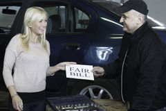 Cherful customer receiving fair bill. A happy customer is receiving a fair bill from the mechanic royalty free stock photo