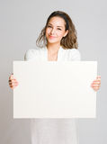 Chherful young brunette with blank banner. Royalty Free Stock Photo