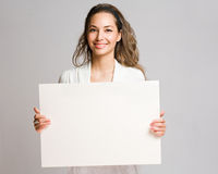 Chherful young brunette with blank banner. Royalty Free Stock Image