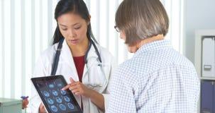 Chińczyka doktorski opowiadać pacjent o xrays zdjęcie royalty free