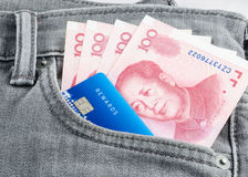 Chińczyka Juan banknot i kredytowa karta w popielatym cajgu wkładać do kieszeni Zdjęcia Stock