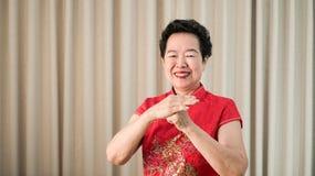 Chińska Azjatycka starsza kobieta w czerwonym kostiumowym nowego roku świętowania gescie zdjęcia royalty free